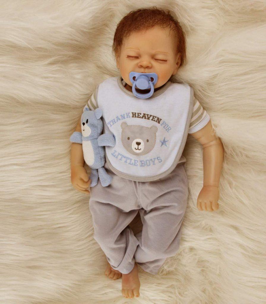 Ce bébé reborn garçon a les yeux clos.
