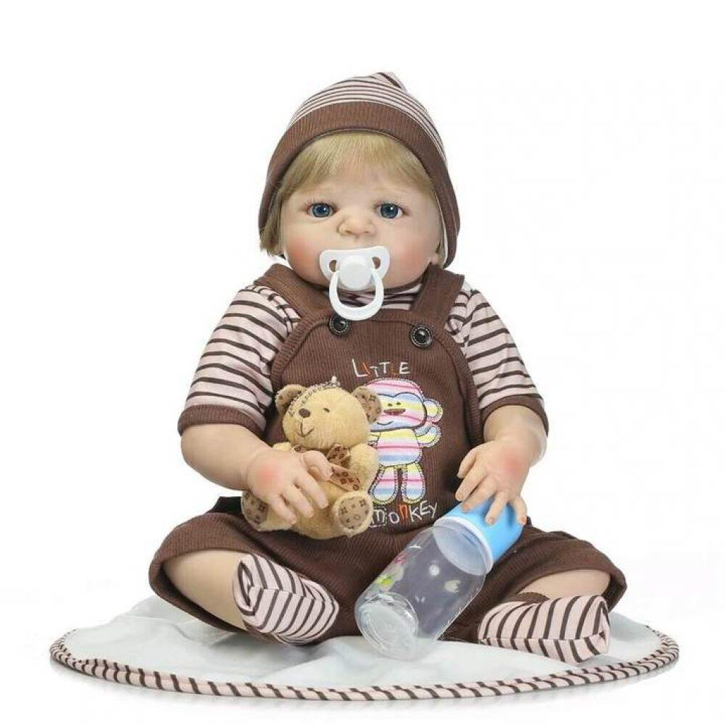 Le bébé reborn Mattéo est livré avec son biberon et son ours en peluche.