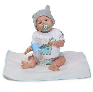 Ce bébé reborn garçon est vêtu d'une grenouillère et d'un bavoir à motifs dinosaures.