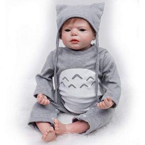 Ce bébé reborn est un garçon vêtu d'habits gris.