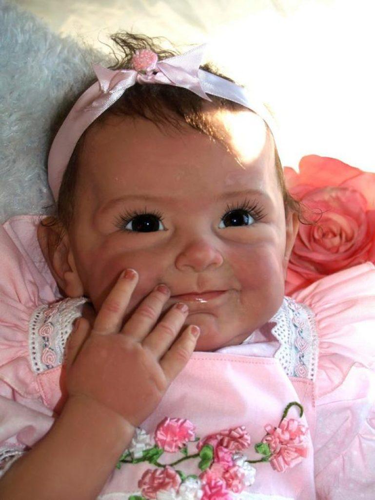 Le bébé reborn Lili peut se toucher le visage avec ses petites mains.