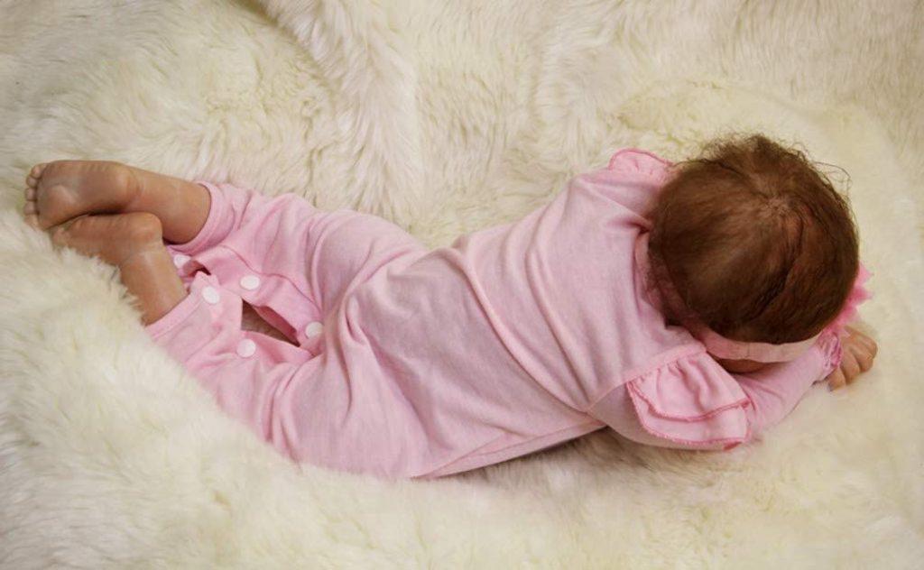 Cette poupée réaliste est allongée sur le ventre.