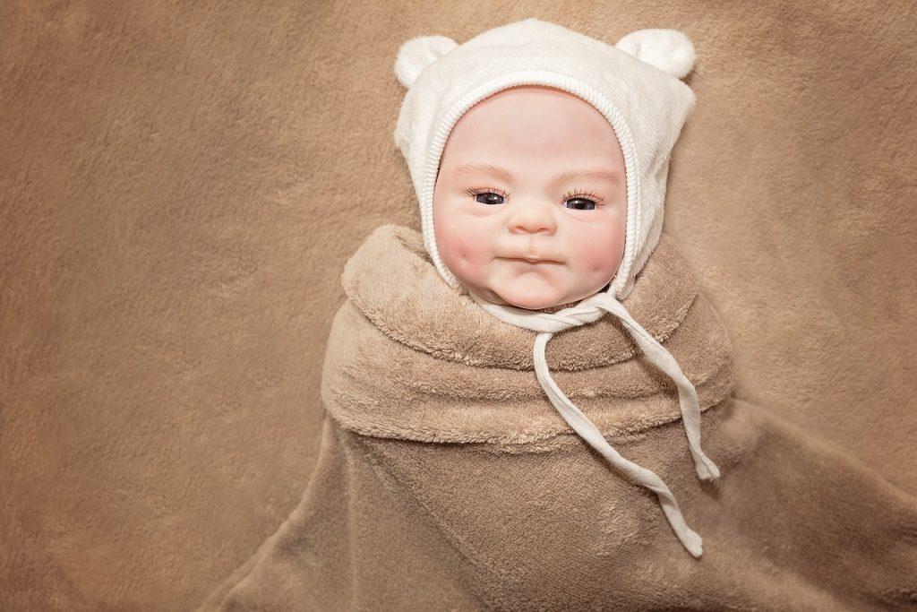 Ce bébé reborn porte un joli bonnet.