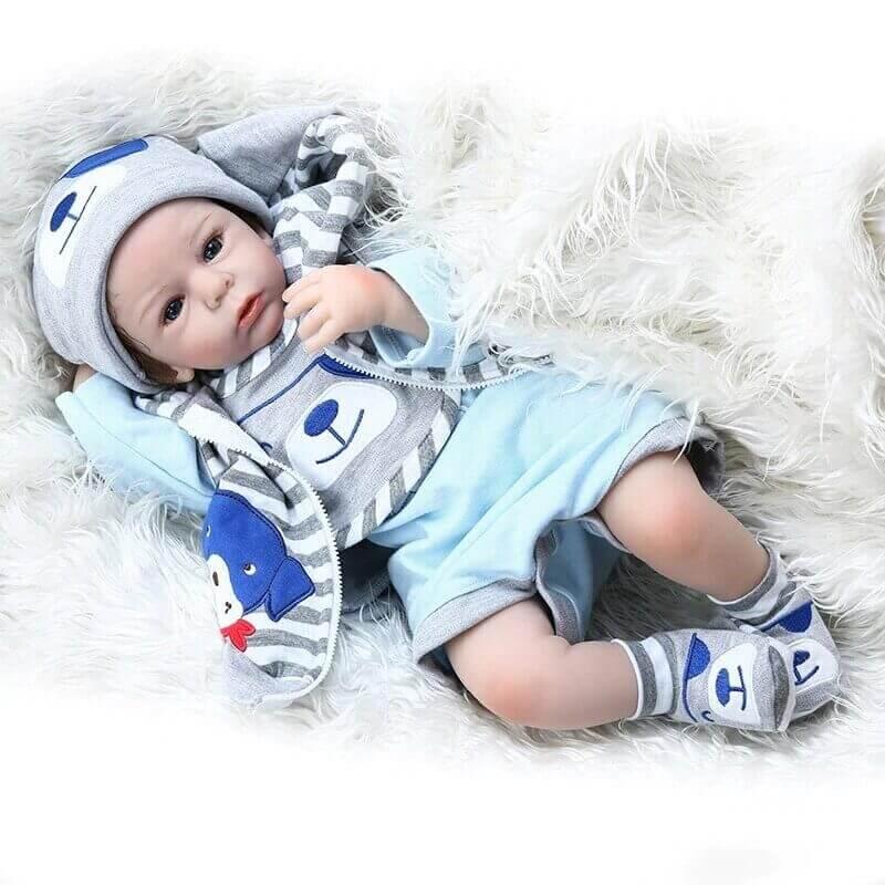 Le bébé reborn garçon Adam porte un bel ensemble bleu et gris.