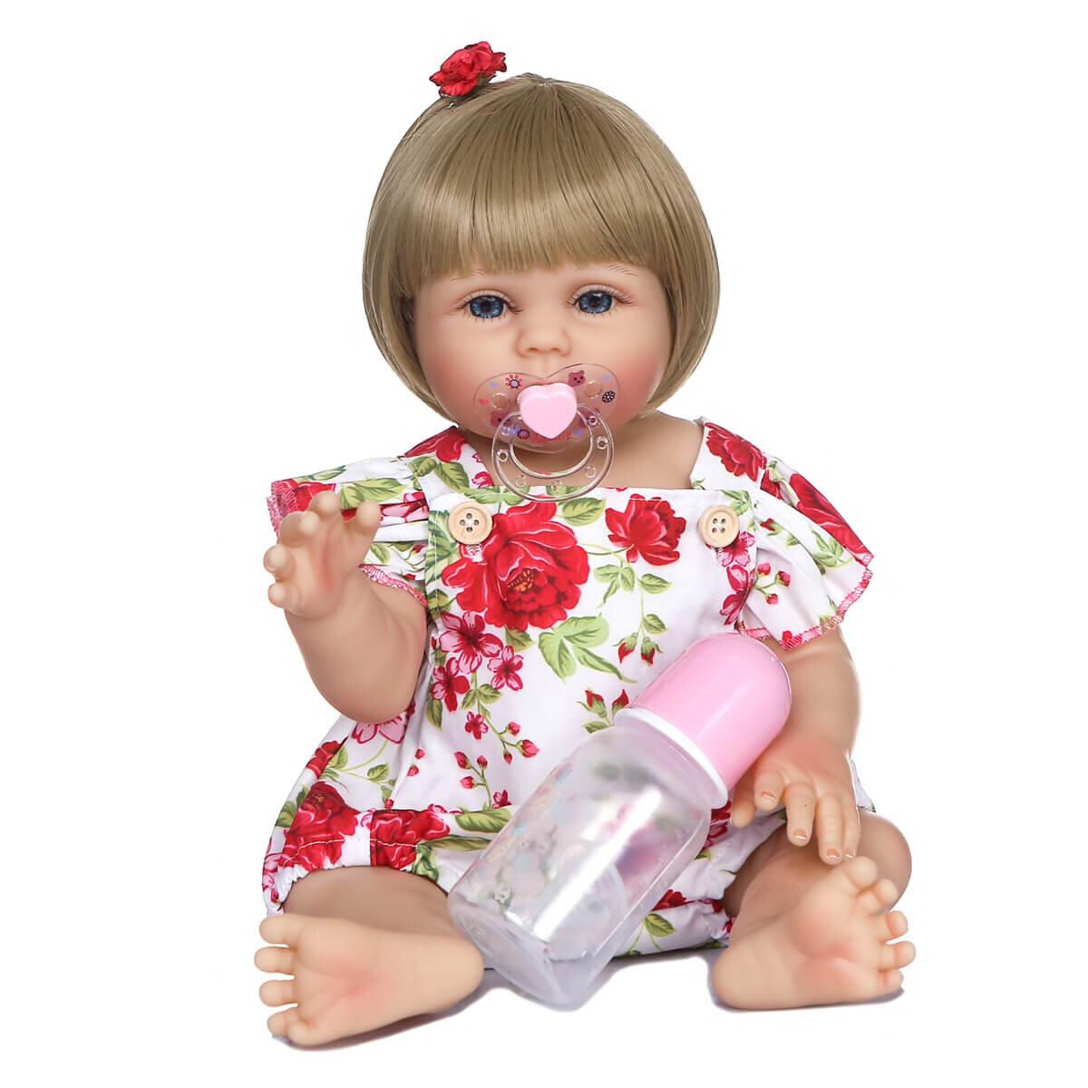 Cette poupée reborn a une tenue fleurie.