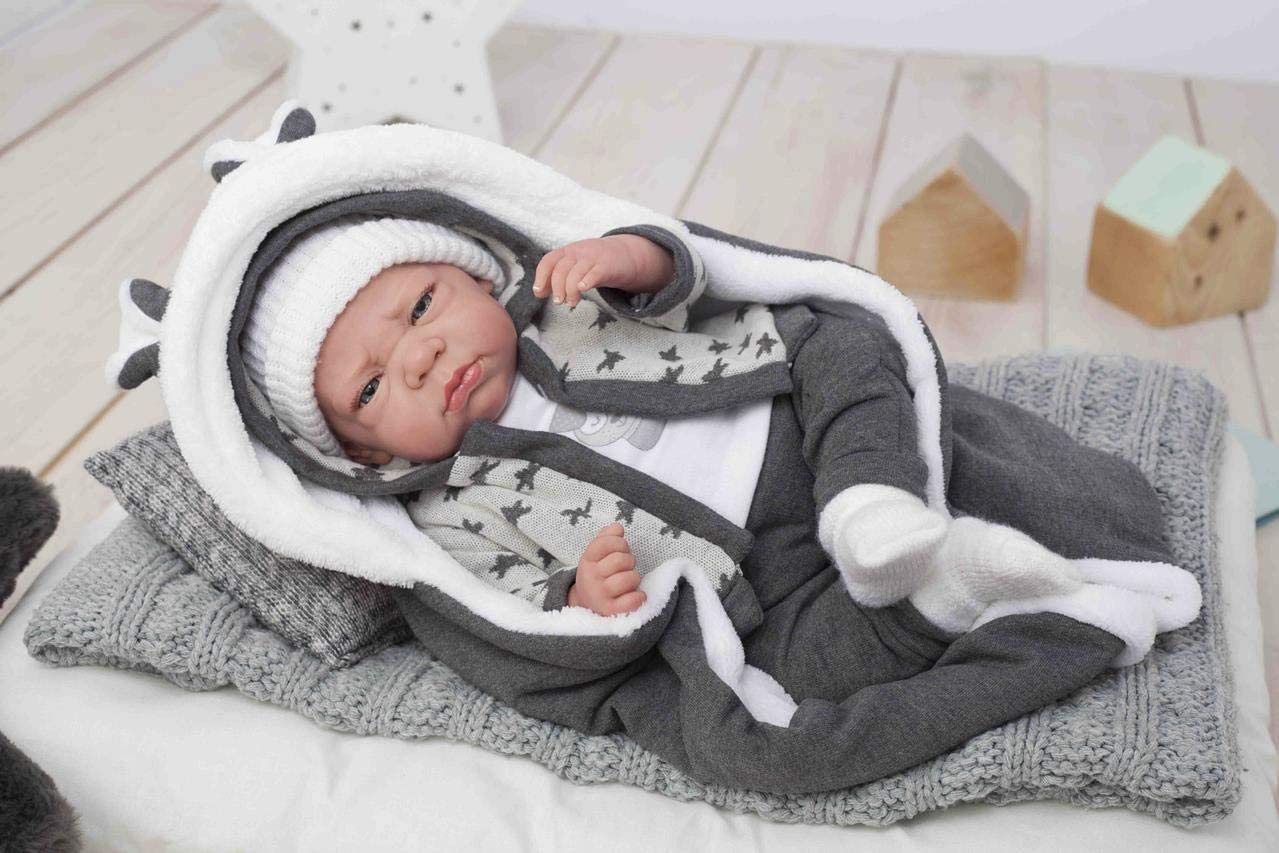 Le bébé reborn garçon Onaï porte un bonnet blanc.