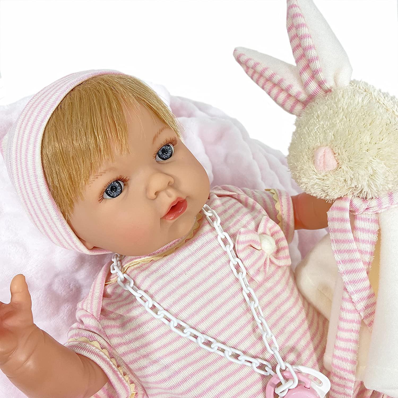 Le bébé reborn avec son doudou lapin Nines d'Onil a un ensemble à rayures blanches et roses.