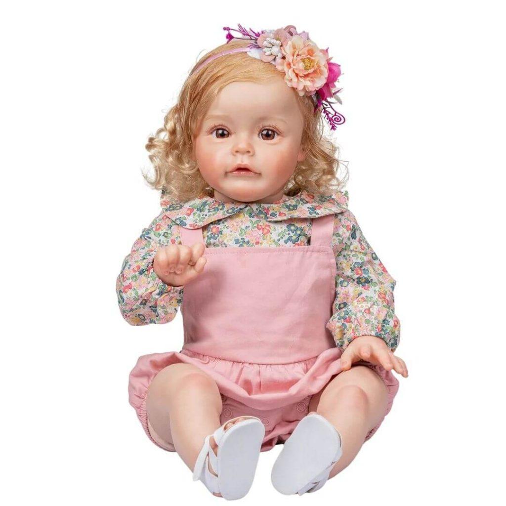 Le bébé reborn fille Chiara a des fleurs dans ses cheveux.