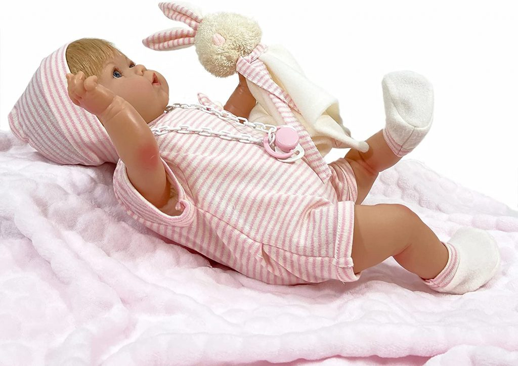 Le reborn baby Nines d'Onil avec son doudou lapin est une petite fille aux cheveux blonds et au corps en tissu.