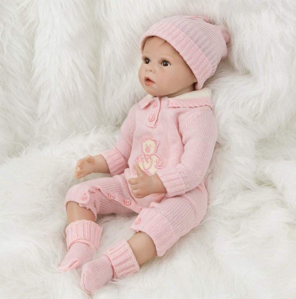 Ce baby reborn aux yeux marrons porte un ensemble en tricot rose.