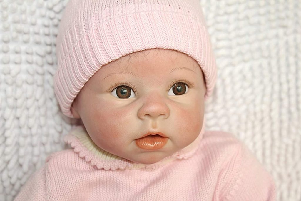 Le visage de cette poupée reborn aux yeux marrons semble réel.