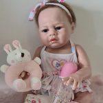 Le bébé reborn fille Aline a un bandeau dans ses cheveux.
