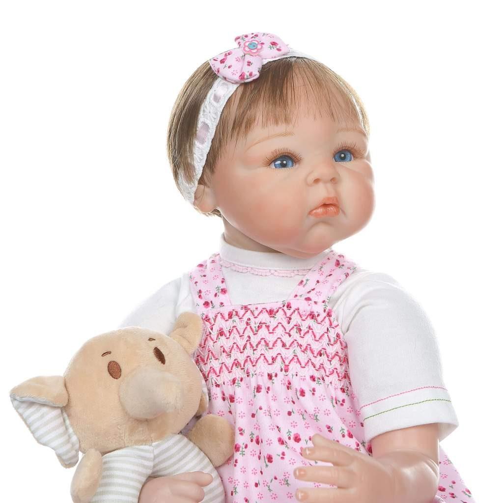 Le bébé reborn fille Enola porte une robe rose.