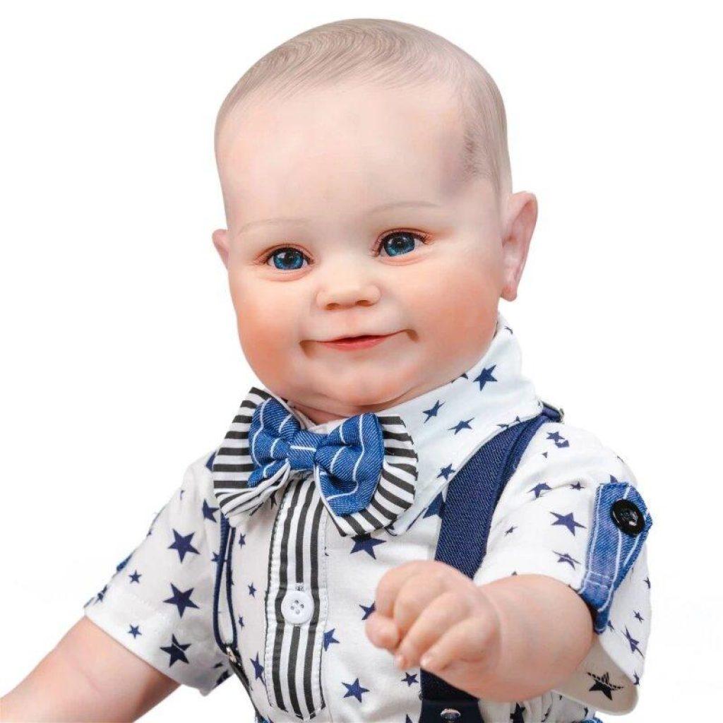Le poupon reborn Tristan a un minois souriant.